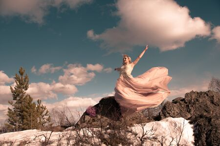 Blonde girl in a pink long dress in a jump on top of a mountain against the sky and clouds and sun