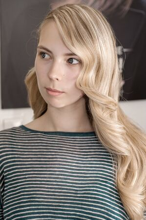 Blonde girl with long hair in a beauty salon with wave hairstyle for prom