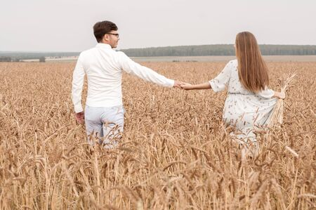 Young couple in a wheat field on a sunny day Foto de archivo