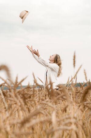 Junge blonde Frau in einem weißen Hemd in einem Weizenfeld wirft im Sommer einen Strohhut in den Himmel