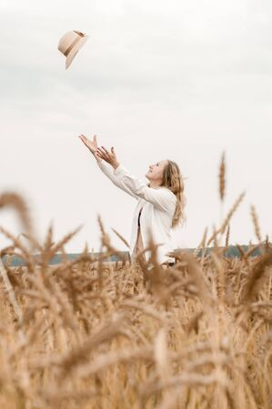 Young blonde woman in a white shirt in a wheat field throws a straw hat into the sky in summer