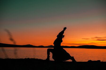 Silhouette of a girl in a dress in a yoga pose on the background of a beautiful orange sunset on the shore of Lake Zyuratkul, Chelyabinsk region, Russia
