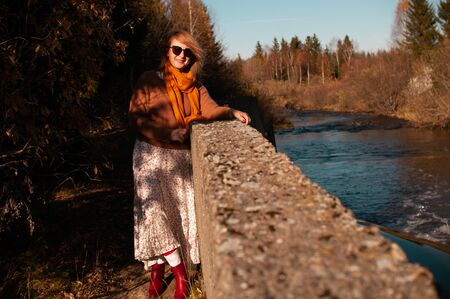 Blond woman dressed in boho style by a river canal in a forest zone