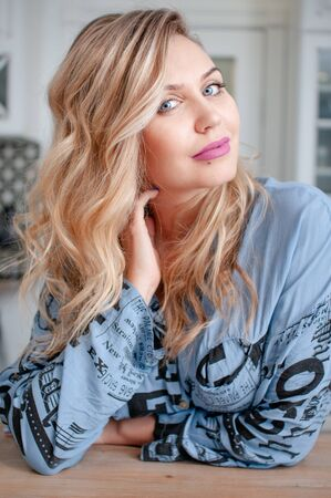 Portrait of a blonde girl with long curly hair and blue eyes in a beauty salon