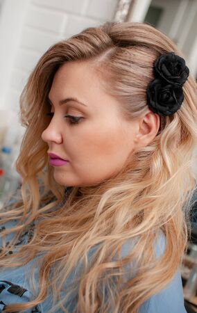 Portrait of a blonde girl with long curly hair in profile at a beauty salon
