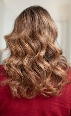 Woman with long brown hair and wavy hairdo in a beauty salon