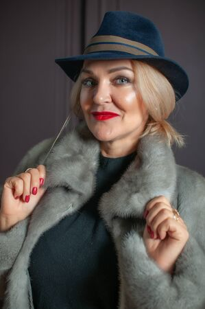 Portrait of an adult woman in a hat and a fur coat in studio