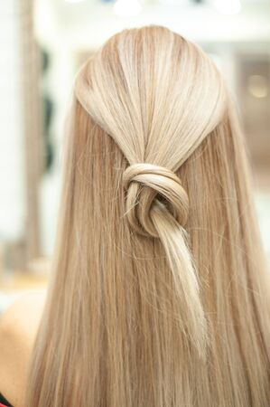 Blonde hair tied in a knot from the back in a beauty salon