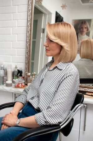 Bobcare haircut with bangs on a blonde woman in profile in a beauty salon