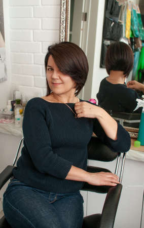 Brunette woman with short bob haircut in a beauty salon in casual clothes without makeup Reklamní fotografie