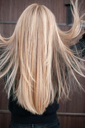 Blonde hair with streaked strands on young woman indoors close-up back view