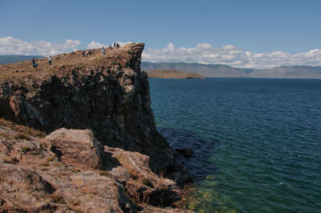 Cape on Lake Baikal with people on a sunny summer day