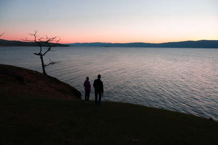 Silhouettes of a man and a woman on the shore of Lake Baikal after sunset on a red and blue background in summer