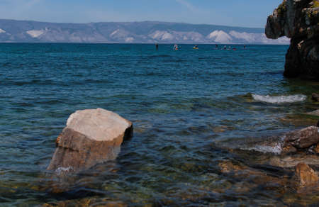 View of Lake Baikal on a rocky coast and people on sap surfing on the water on a summer sunny day