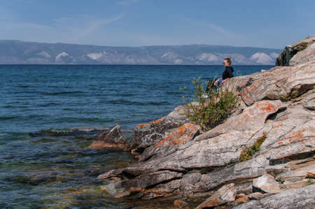 woman sits on the rocky shore of Lake Baikal near the water on a summer sunny day 版權商用圖片