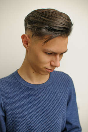 Young man with modern short haircut in beauty salon