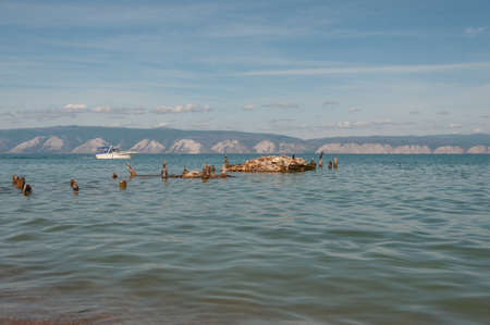 Lake Baikal with a view of the water stones and birds Cormorant and the opposite mountainous shore on a summer sunny day