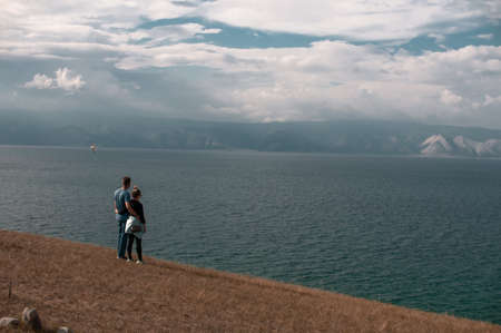 Young couple man and woman stand on the shore of Lake Baikal on a summer sunny day Reklamní fotografie