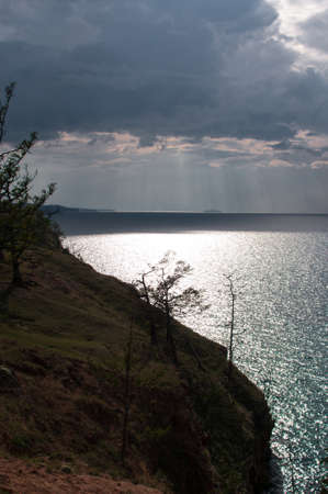 Coastline of Lake Baikal with a cape of dark clouds and sunlight on a summer day