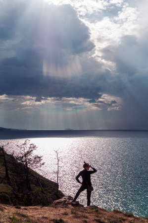 Woman looks at a picturesque view of Lake Baikal and the sun's rays falling on the water