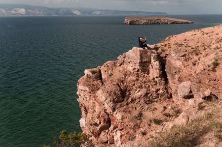 Woman sits on the top of a rock and looks at a picturesque view of Lake Baikal on a summer day