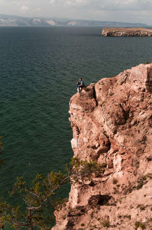 Man on the edge on a high rock on Lake Baikal in Siberia Russia in summer on a sunny day