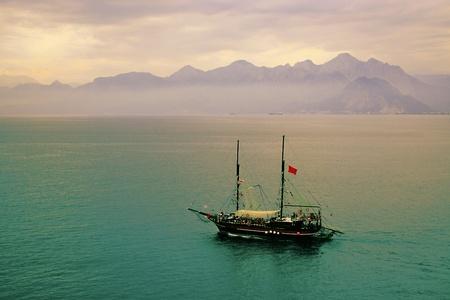 Mystic ship sailing in the sea around Antalya, Turkey at sunset