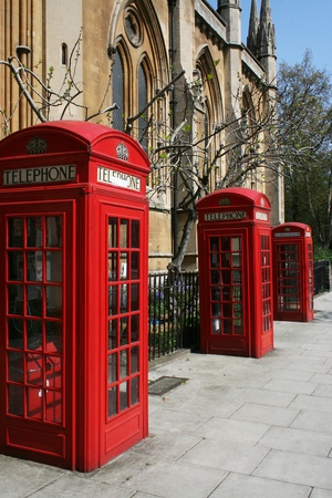 gilbert: Three red telephone booths on a London street