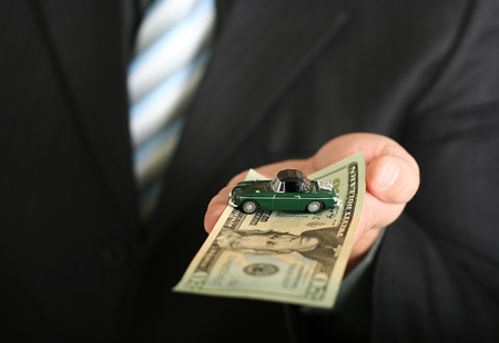 sales agent: Sales agent offering car, holding a toy car and a dollar bill Stock Photo