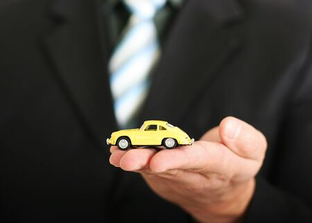 Sales agent offering car, holding a toy car Stock Photo - 12519739