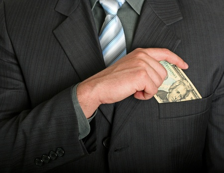 Businessman putting a dollar bill in his pocket Stock Photo - 12519757
