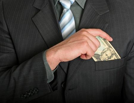 Businessman putting a dollar bill in his pocket Archivio Fotografico