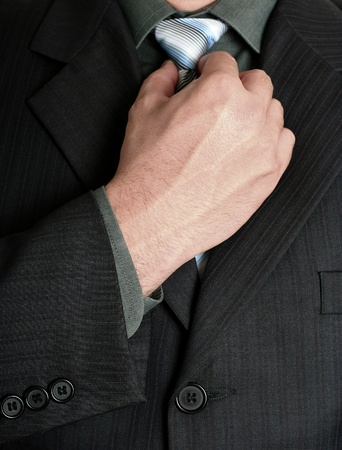 Businessman tweaking his tie with a hand