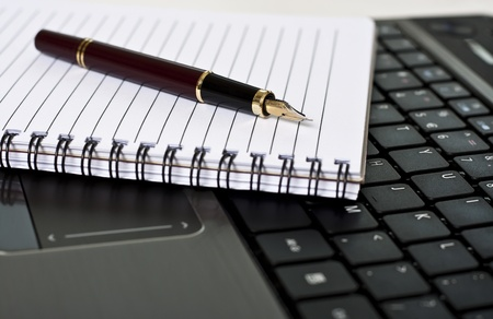 Pen, notepad and laptop on the desk in the office Stock Photo