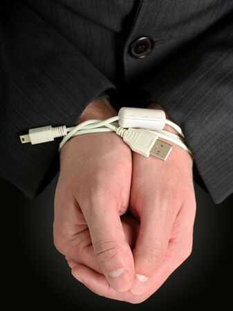 cuffed: Businessman hands tied with an USB cable