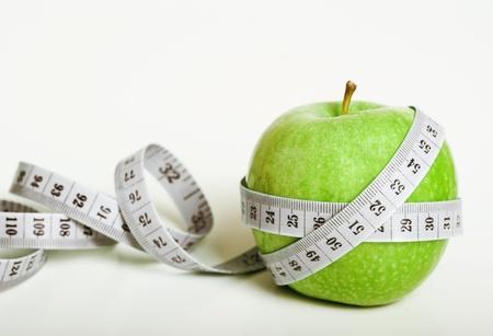 Fresco verde mela con nastro di misura su sfondo bianco Archivio Fotografico - 13330552
