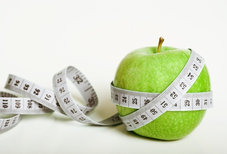 Fresh green apple with measuring tape on white background photo