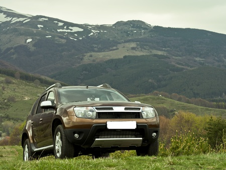 Off road toursim adventure with a 4x4 car parked on a sloped meadow in the mountain