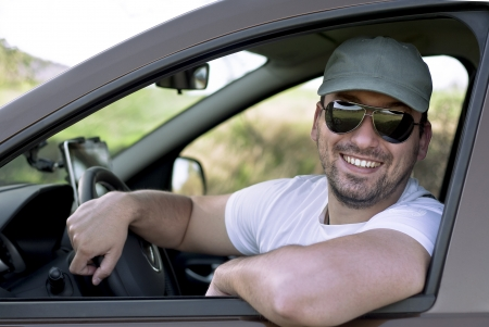 Happy male driver smiling while sitting in a car with open front window. Selective focus. Stock Photo