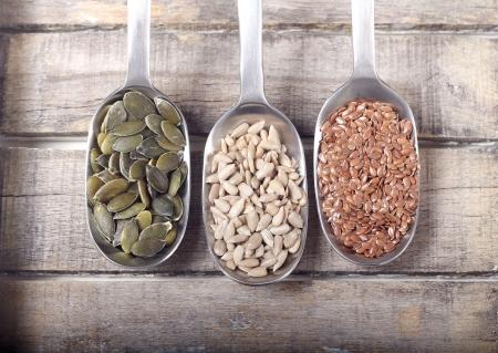 semillas de girasol: Cucharas llenas de semillas sobre fondo de madera