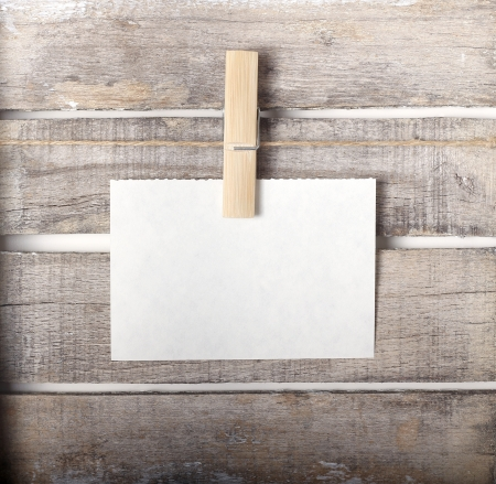 Paper note with a pinch on wooden background Stock Photo
