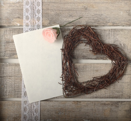 Pink roses and heart on wooden background - greeting card or invitation