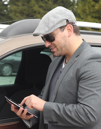 Happy male driver smiling while standing by a car with open front window and checking using internet via tablet. Selective focus.