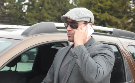 Confident businessman standing by a car with open front window and talking over mobile phone. Selective focus.