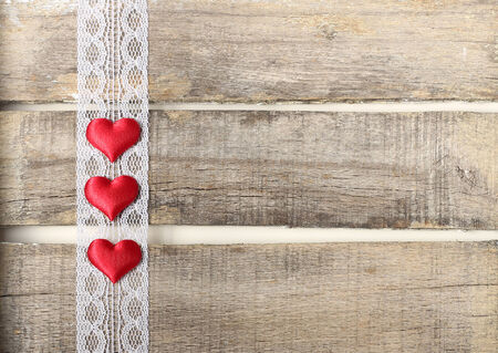 Three red hearts on old wooden background with lace