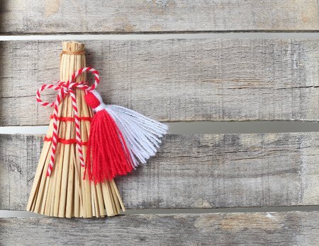 Red and white martenitsa with broom on old wooden background with lace Archivio Fotografico