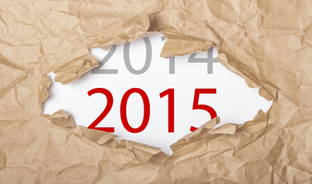torn cardboard: Upcoming New Year 2015 showing up on paper under torn cardboard