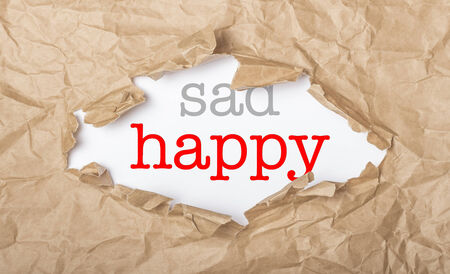 Happy and sad words on white paper with copy space and torn cardbox