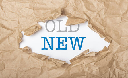 New and old words on white paper with copy space and torn cardbox Stock Photo