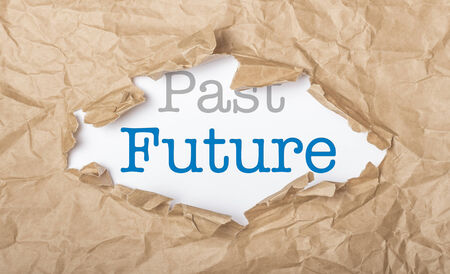 Future and past words on white paper with copy space and torn cardbox